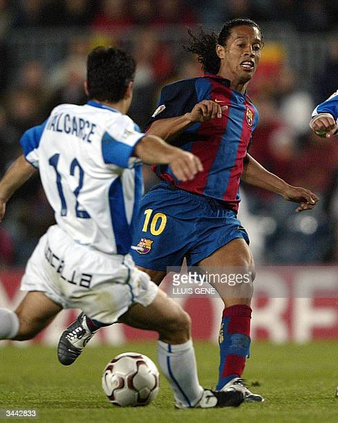 Barcelona's Brazilian Ronaldinho vies with CF Malaga's Valcarce during their Spanish League football match at Camp Nou Stadium in Barcelona 18 April...