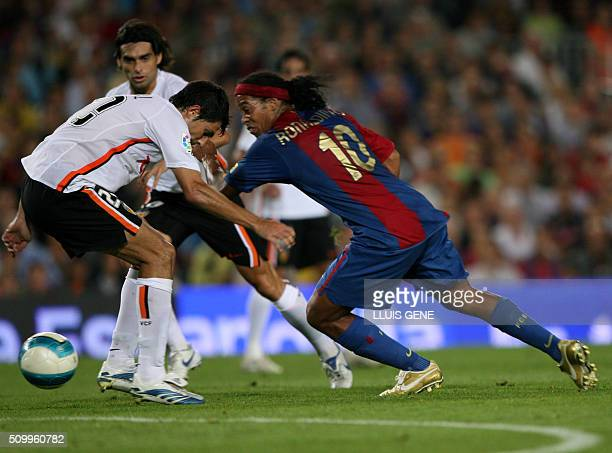 FC Barcelona's Brazilian Ronaldinho vies with Valencia's Moretti during their Spanish League football match at Camp Nou stadium in Barcelona 24...