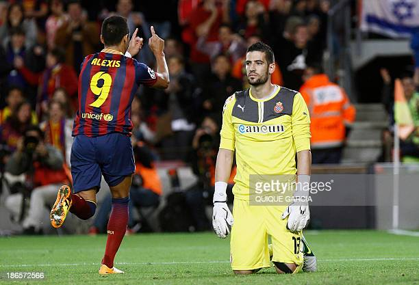 Barcelona's Chilean forward Alexis Sanchez celebrates next to Espanyol's goalkeeper Kiko Casilla after scoring during the Spanish league football...