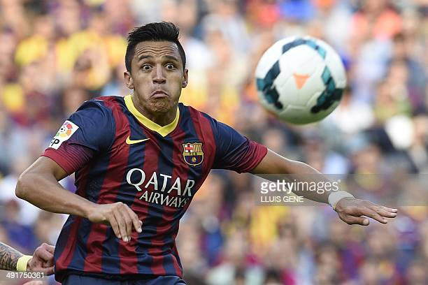 Barcelona's Chilean forward Alexis Sanchez eyes the ball during the Spanish league football match FC Barcelona vs Club Atletico de Madrid at the Camp...