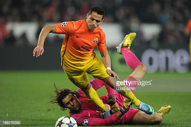Barcelona's Chilean forward Alexis Sanchez is tackled by Paris Saint-Germain's Italian goalkeeper Salvatore Sirigu to give away a penalty during the...