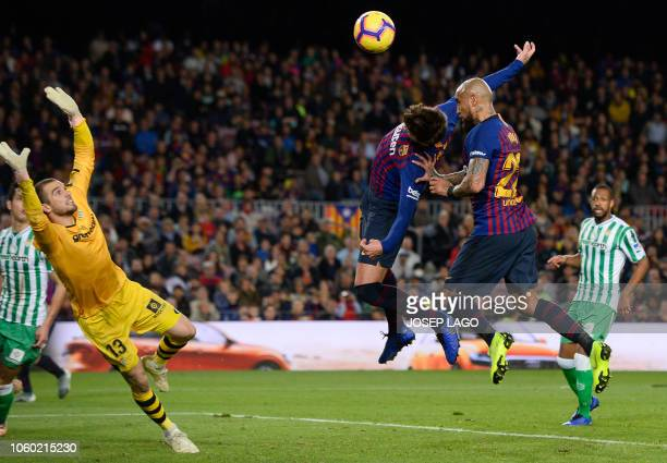 TOPSHOT Barcelona's Chilean midfielder Arturo Vidal and Barcelona's Spanish defender Gerard Pique jump to tead the ball during the Spanish league...