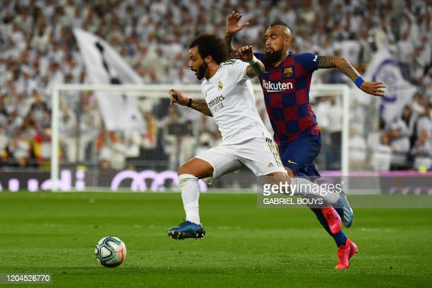 Barcelona's Chilean midfielder Arturo Vidal challenges Real Madrid's Brazilian defender Marcelo during the Spanish League football match between Real...