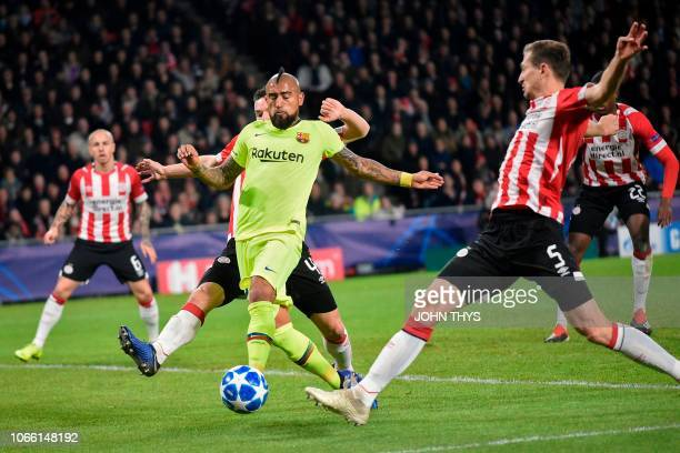 Barcelona's Chilean midfielder Arturo Vidal vies with Eindhoven's defender Daniel Schwaab during the UEFA Champions League football match between PSV...