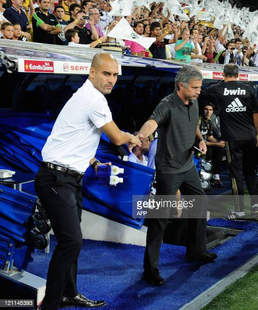 Barcelona's coach Josep Guardiola and Real Madrid's Portuguese coach Jose Mourinho shake hands before the Spanish Supercup first leg football match...