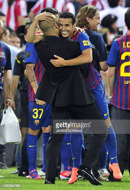 Barcelona's coach Josep Guardiola embraces Barcelona's forward Pedro Rodriguez at the end of the Spanish King's Cup final football match between...
