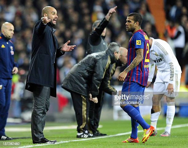 Barcelona's coach Josep Guardiola gestures in front of Barcelona's Brazilian defender Dani Alves during the Spanish Cup 'El clasico' football match...