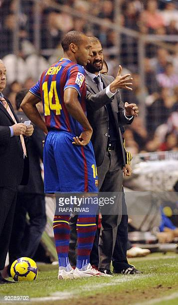 SCORE Barcelona's coach Josep Guardiola talks to French Thierry Henry during a Spanish league football match on November 21 at San Mames stadium in...
