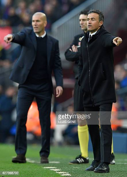 Barcelona's coach Luis Enrique and Real Madrid's French coach Zinedine Zidane gesture from the sideline during the Spanish league football match FC...