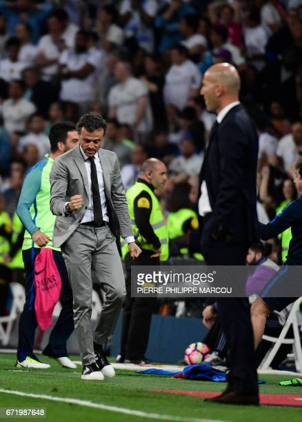 Barcelona's coach Luis Enrique celebrates their third goal beside Real Madrid's French coach Zinedine Zidane during the Spanish league football match...