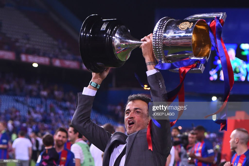 TOPSHOT - Barcelona's coach Luis Enrique holds up the cup after the team won the Spanish Copa del Rey (King's Cup) final football match FC Barcelona vs Deportivo Alaves at the Vicente Calderon stadium in Madrid on May 27, 2017. Barcelona won 3-1. / AFP PHOTO / Josep LAGO