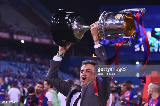 TOPSHOT Barcelona's coach Luis Enrique holds up the cup after the team won the Spanish Copa del Rey final football match FC Barcelona vs Deportivo...