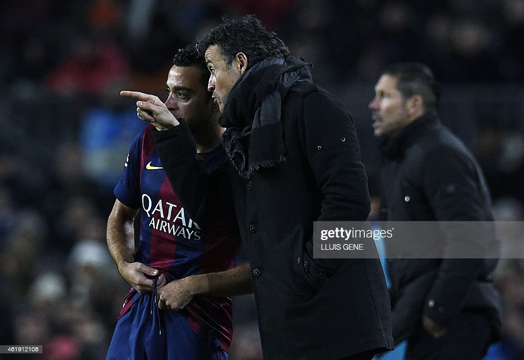 Barcelona's coach Luis Enrique talks with Barcelona's midfielder Xavi Hernandez during the Spanish Copa del Rey (King's Cup) quarter final first leg football match FC Barcelona vs Atletico de Madrid at the Camp Nou stadium in Barcelona on January 8, 2015.