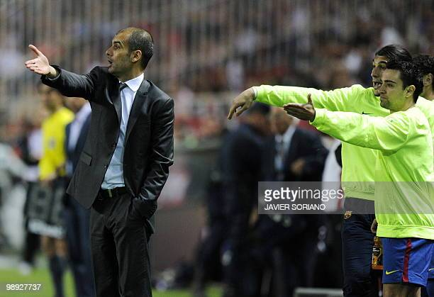 Barcelona's coach Pep Guardiola gestures next to Barcelona's midfielder Xavi Hernandez during their Spanish league football match beetwen Sevilla and...