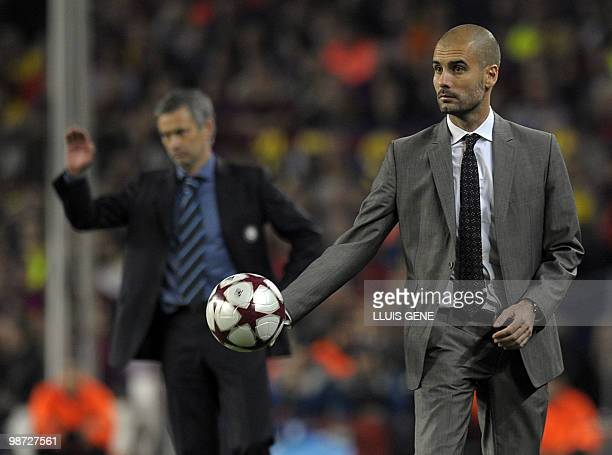 Barcelona's coach Pep Guardiola holds the ball next to Inter Milan's Portuguese coach Jose Mourinho during the UEFA Champions League semifinal second...