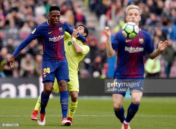 Barcelona's Colombian defender Yerry Mina hits Getafe's Spanish forward Angel Rodriguez as Barcelona's Croatian midfielder Ivan Rakitic controls the...
