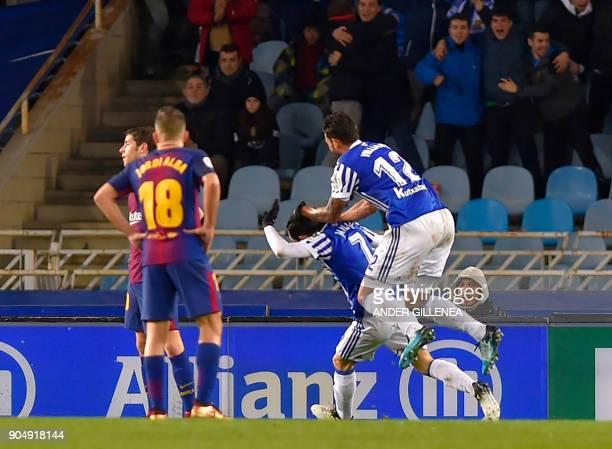 Barcelona's Croatian midfielder Ivan Rakitic and Barcelona's Uruguayan forward Luis Suarez stand on the field after Real Sociedad's opening goal...