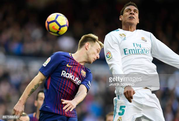 Barcelona's Croatian midfielder Ivan Rakitic and Real Madrid's French defender Raphael Varane jump for the ball during the Spanish League 'Clasico'...
