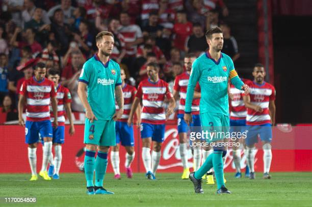 Barcelona's Croatian midfielder Ivan Rakitic and Spanish defender Gerard Pique react to Granada's Nigerian midfielder Ramon Azeez' goal during the...