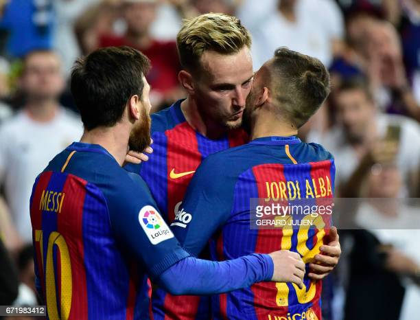 Barcelona's Croatian midfielder Ivan Rakitic celebrates a goal kissing Barcelona's defender Jordi Alba beside Barcelona's Argentinian forward Lionel...