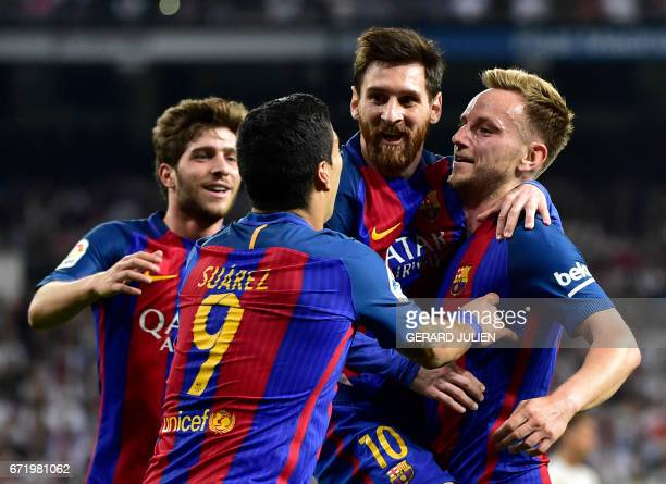Barcelona's Croatian midfielder Ivan Rakitic celebrates a goal with Barcelona's Argentinian forward Lionel Messi and Barcelona's Uruguayan forward...