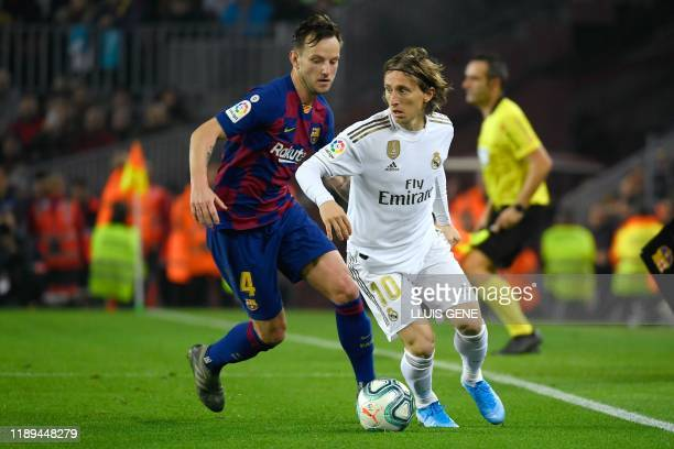 Barcelona's Croatian midfielder Ivan Rakitic challenges Real Madrid's Croatian midfielder Luka Modric during the El Clasico Spanish League football...