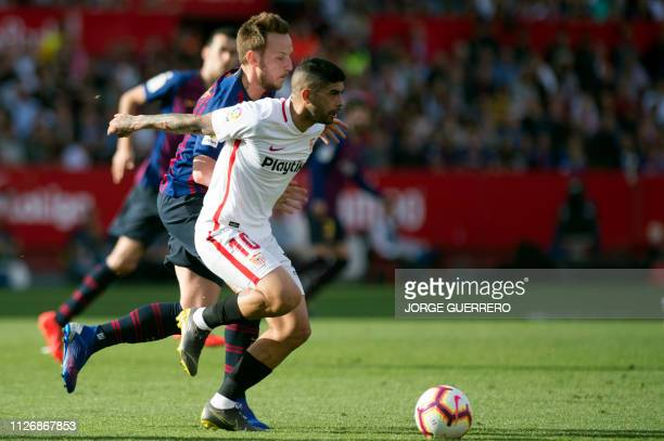 Barcelona's Croatian midfielder Ivan Rakitic fights for the ball with Sevilla's Argentinian midfielder Ever Banega during the Spanish league football...