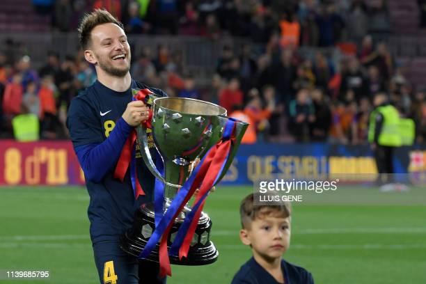 Barcelona's Croatian midfielder Ivan Rakitic holds the trophy as he celebrates becoming La Liga champions after winning the Spanish League football...