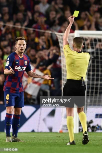 Barcelona's Croatian midfielder Ivan Rakitic receives a yellow card during the El Clasico Spanish League football match between Barcelona FC and Real...