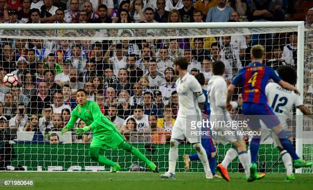 Barcelona's Croatian midfielder Ivan Rakitic shoots to score a goal during the Spanish league football match Real Madrid CF vs FC Barcelona at the...