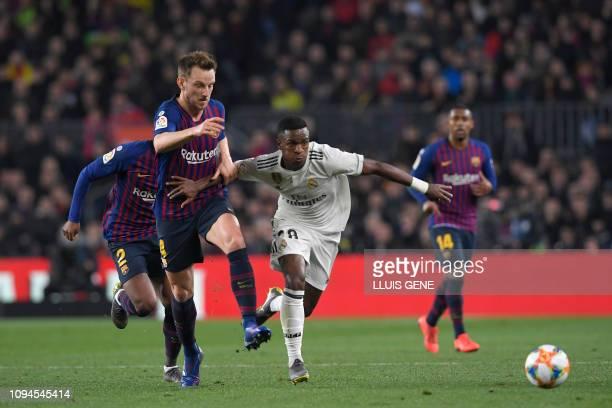 Barcelona's Croatian midfielder Ivan Rakitic vies for the ball with Real Madrid's Brazilian forward Vinicius Junior during the Spanish Copa del Rey...