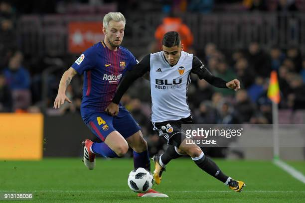 Barcelona's Croatian midfielder Ivan Rakitic vies for the ball with Valencia's Brazilian forward Andreas Pereira during the Spanish 'Copa del Rey'...