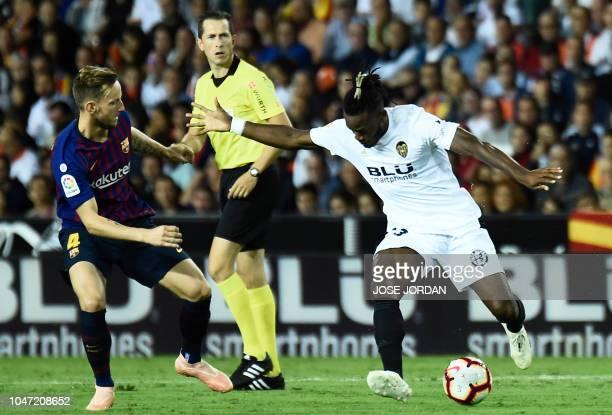 Barcelona's Croatian midfielder Ivan Rakitic vies with Valencia's Belgian forward Michy Batshuayi during the Spanish league football match between...