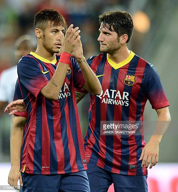 Barcelona's defender Carles Planas reacts with teammate Neymar while leaving the pitch with teammates after their preseason friendly football match...