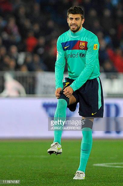Barcelona's defender Gerard Pique adjusts his sock during the Spanish King's Cup semifinal secondleg football match UD Almeria vs FC Barcelona on...