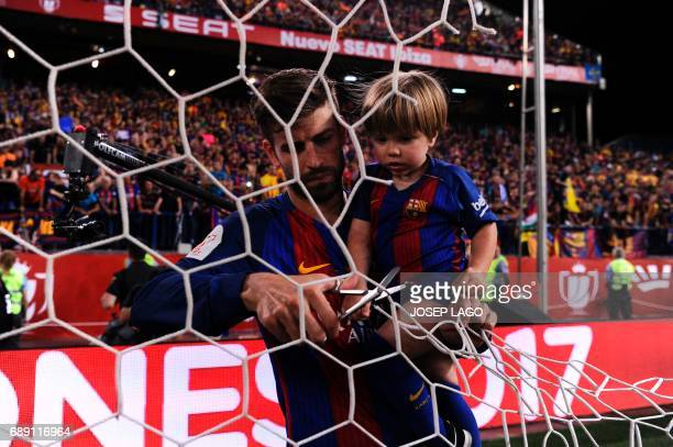 Barcelona's defender Gerard Pique and his son Sasha cuts a part of the net at the end of the Spanish Copa del Rey final football match FC Barcelona...