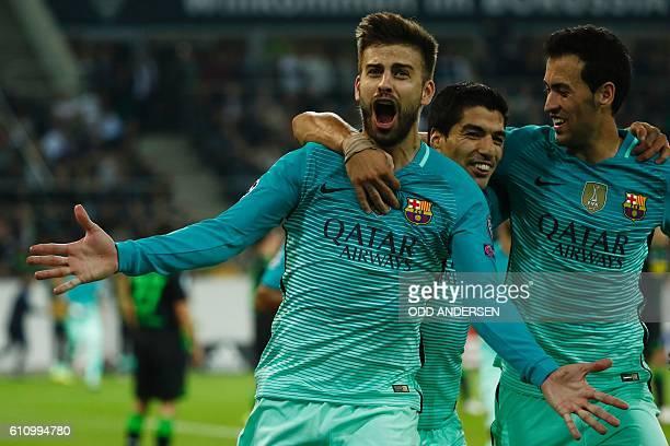 Barcelona's defender Gerard Pique celebrates scoring the 12 goal with his teammates Uruguayan forward Luis Suarez and midfielder Sergio Busquets...