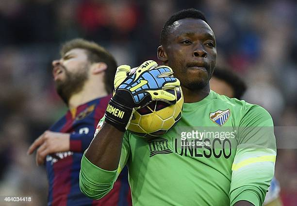 Barcelona's defender Gerard Pique grimaces as Malaga's Cameroonian goalkeeper Carlos Kameni holds the ball during the Spanish league football match...