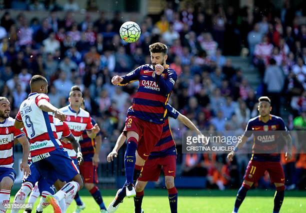 Barcelona's defender Gerard Pique heads the ball during the Spanish league football match Granada CF vs FC Barcelona at Nuevo Los Carmenes stadium in...