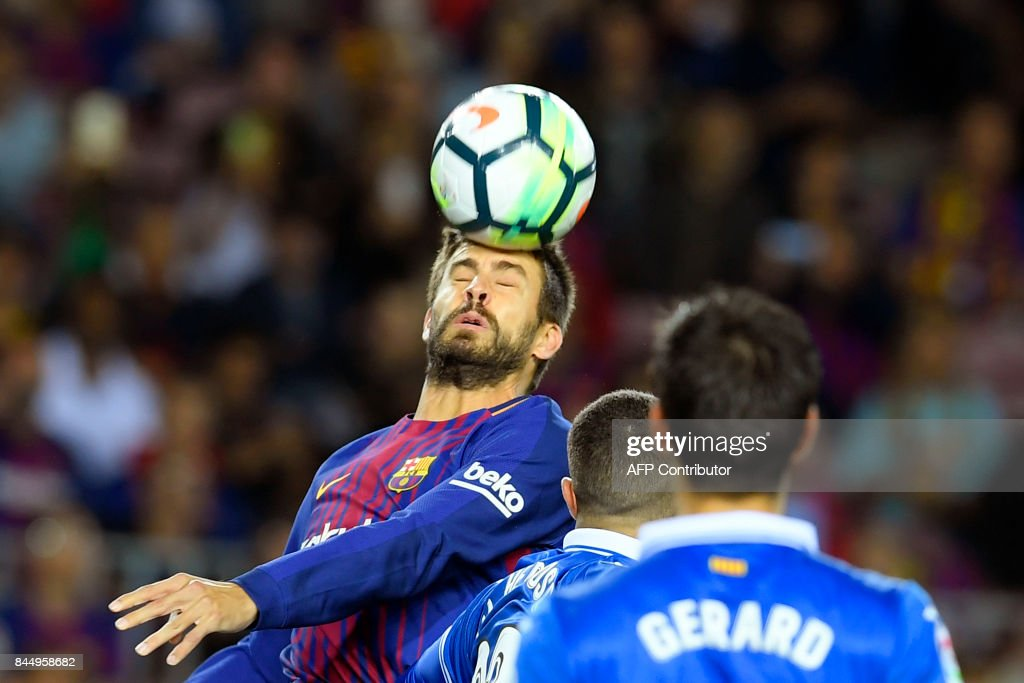 Barcelona's defender Gerard Pique (L) heads the ball during the Spanish Liga football match Barcelona vs Espanyol at the Camp Nou stadium in Barcelona on September 9, 2017. /