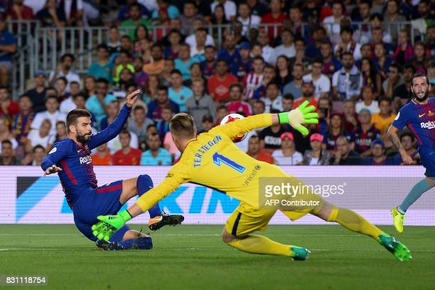 Barcelona's defender Gerard Pique scores an own goal during the first leg of the Spanish Supercup football match between FC Barcelona and Real Madrid...