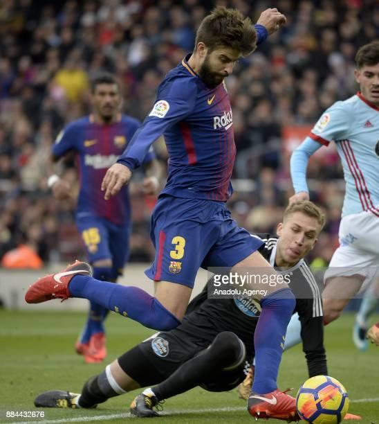 Barcelona's defender Gerard Pique shoots the ball next to Celta's goalkeeper Ruben Blanco during the Spanish league football match between FC...