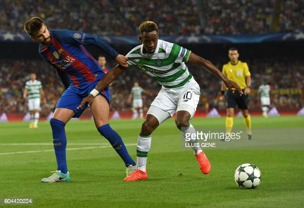 Barcelona's defender Gerard Pique vies with Celtic's French forward Moussa Dembele during the UEFA Champions League football match FC Barcelona vs...
