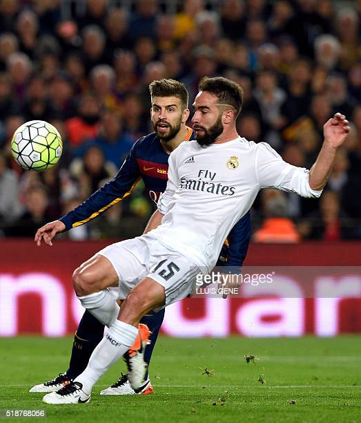 Barcelona's defender Gerard Pique vies with Real Madrid's defender Dani Carvajal during the Spanish league 'Clasico' football match FC Barcelona vs...