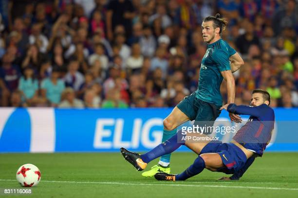 Barcelona's defender Gerard Pique vies with Real Madrid's Welsh forward Gareth Bale during the Spanish Supercup first leg football match FC Barcelona...