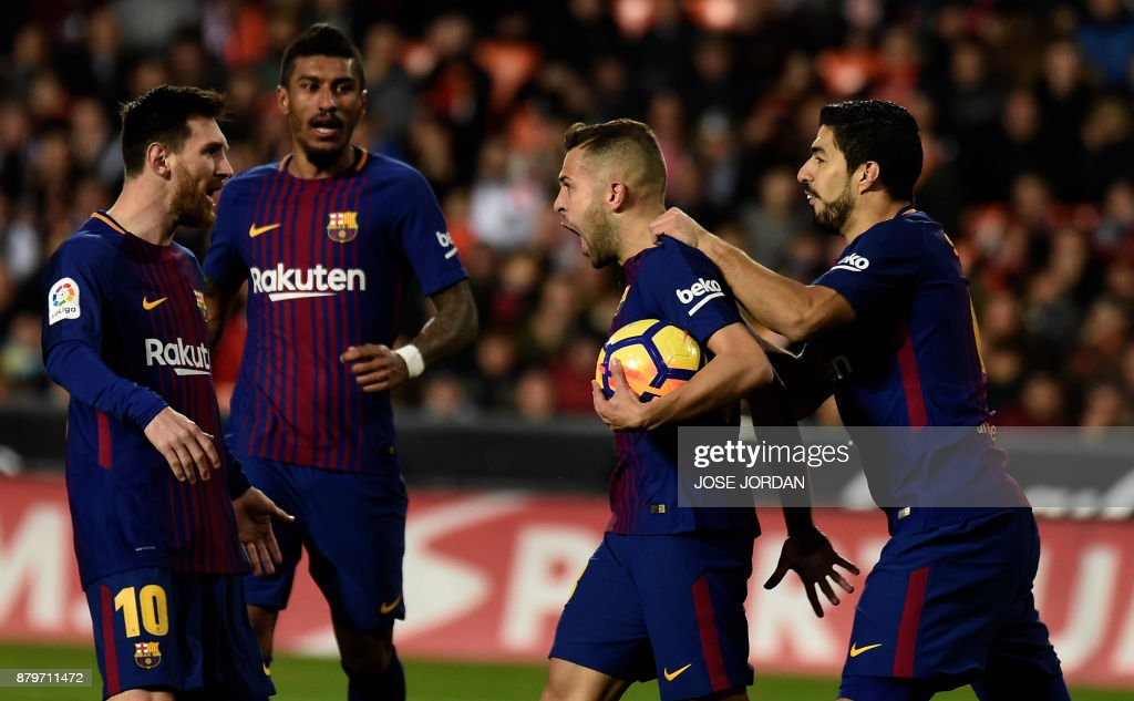 TOPSHOT - Barcelona's defender Jordi Alba (C) celebrates after scoring with Barcelona's Uruguayan forward Luis Suarez Barcelona's Brazilian midfielder Jose Paulinho and Barcelona's Argentinian forward Lionel Messi (R) during the Spanish league football match Valencia CF and FC Barcelona at Mestalla stadium in Valencia on November 26, 2017. /