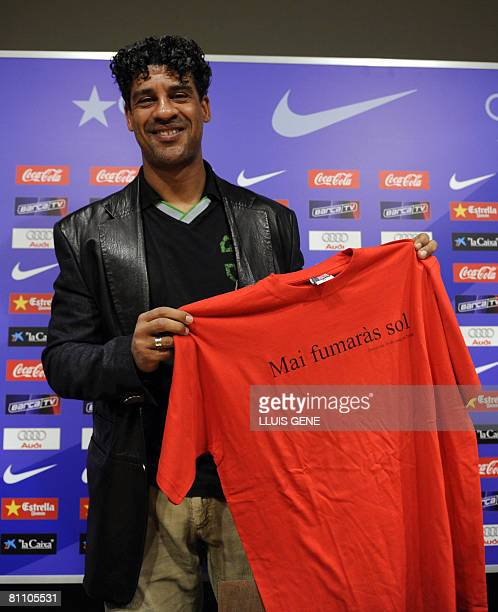 FC Barcelona's Dutch coach Frank Rijkaard shows a Tshirt that says in Catalan you 'never smoked alone' that the journalists have given him during his...