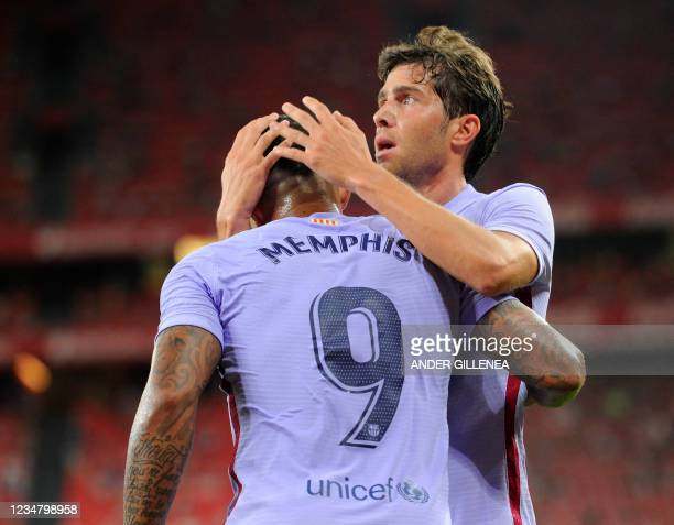 Barcelona's Dutch forward Memphis Depay is congratulated by Barcelona's Spanish midfielder Sergi Roberto for his goal during the Spanish League...