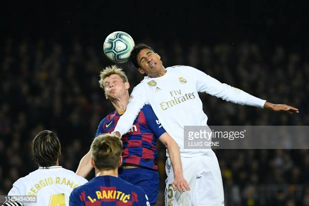 Barcelona's Dutch midfielder Frenkie De Jong and Real Madrid's French defender Raphael Varane jump for the ball during the El Clasico Spanish League...