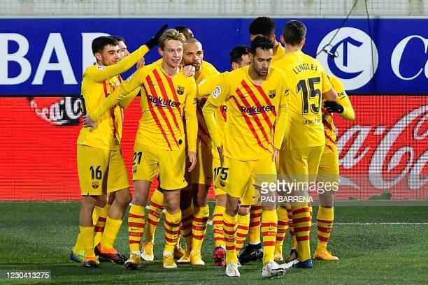 Barcelona's Dutch midfielder Frenkie De Jong celebrates with teammates after scoring a goal during the Spanish League football match between Huesca...